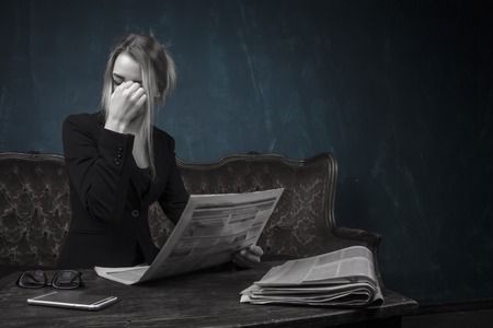 Portrait of a tired business woman reading bad news in the newspaper. concept, world news Stockfoto