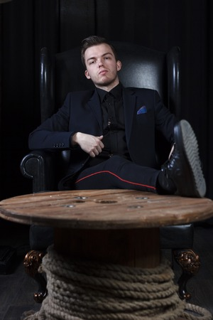 A young man in a suit on the background of an expensive dark interior with a place for advertising or text.