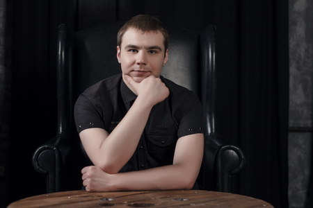 A young man in a black shirt on the background of an expensive dark interior.