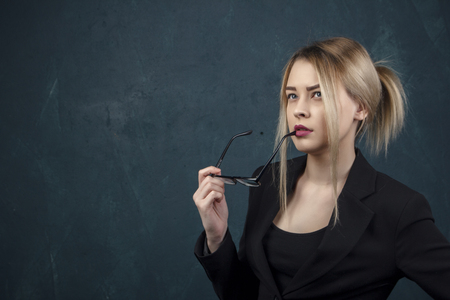 Portrait of a beautiful woman in glasses in a black suit against a blue textural wall with space for text.
