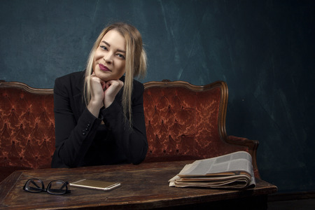 Portrait of a beautiful woman in a black suit who looks directly at the camera in an expensive antique interior against a blue textured wall background with space for text. Business lady, a successful independent young girl.