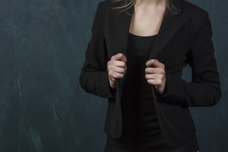 woman in jacket adjusts his hands against the blue wall, close-up with lots of details Stockfoto