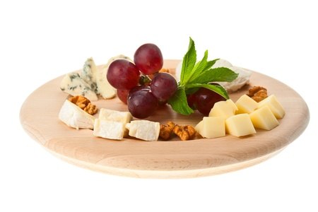 Various types of cheese with nuts and grapes on plate, isolated in white  photo