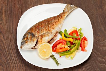 Grilled dorado fish with lemon and vegetables  Standard-Bild