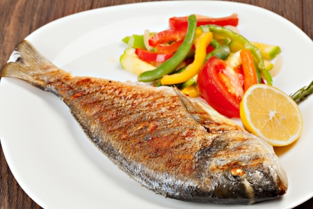 eating fish: Grilled dorado fish with lemon and vegetables  Stock Photo