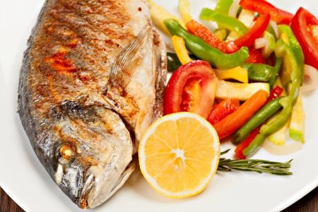 Grilled dorado fish with lemon and vegetables  Imagens