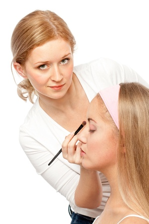 ceremonial make up: Beautician Applying Womans Make Up.Isolated on white