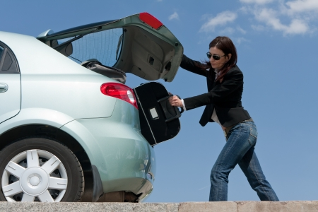 woman packing her baggage into the car photo