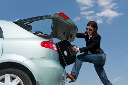 mujer preparando su equipaje en el coche