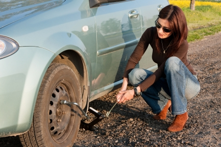 woman changing the broken Tire photo