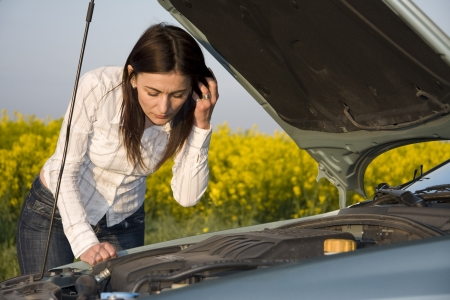 busted: woman looking in the broken engine Stock Photo