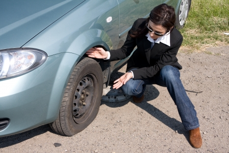 woman and the car with punctured wheel