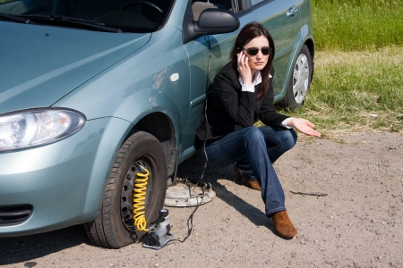 roadside assistance: woman with damaged car calling for help