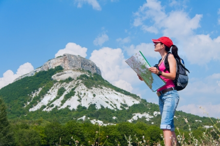 woman with the map and binoculars in the mountains Standard-Bild