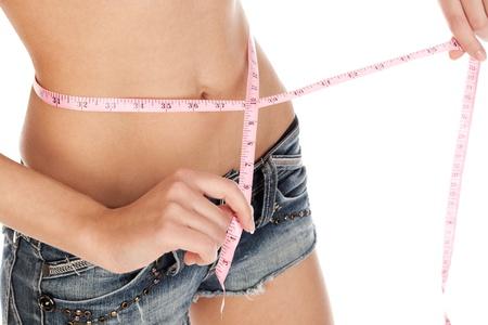 skinny: Joven mujer medici�n de la cintura sobre un fondo blanco Foto de archivo