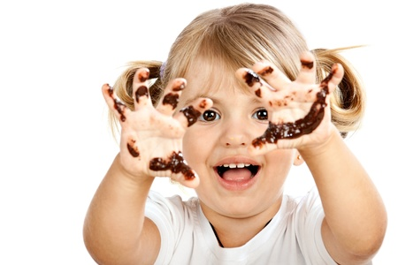 dirty blond: Small girl with chocolate smeared all over her face and fingers. Stock Photo