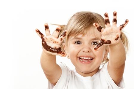 poco: Pequeña muchacha con el chocolate untado toda la cara y los dedos. Foto de archivo