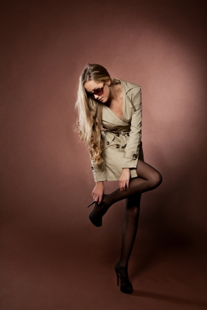 blond brown: Young blonde woman in topcoat studio shot on brown  background Stock Photo