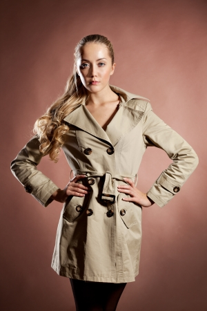 topcoat: Young blonde woman in topcoat studio shot on brown  background Stock Photo
