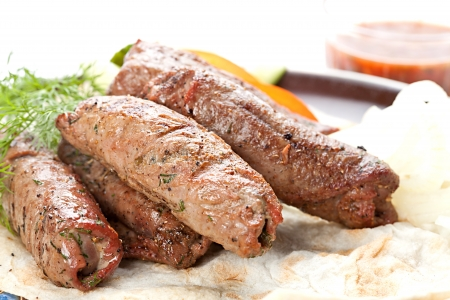 Grilled  sausages with vegetables and sauce on the flat unleavened wheat bread photo