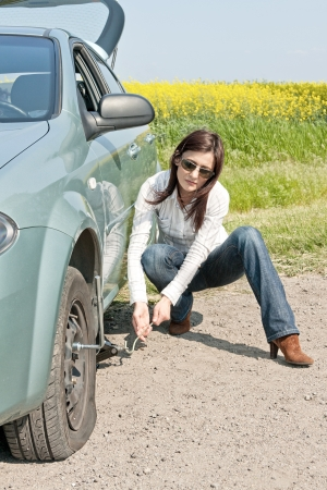 woman and the car with punctured wheel photo