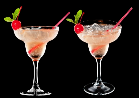 aperitive: A couple of identical alcoholic cocktails on the black background