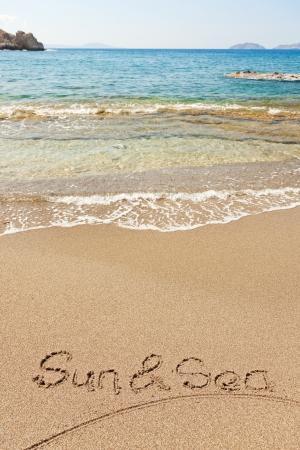 Sun and sea written in a sandy tropical beach photo