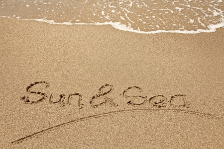 Sun and sea  written in a sandy tropical beach photo