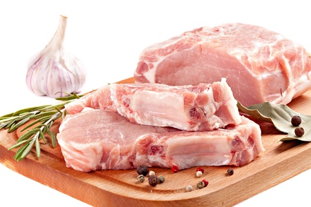 fresh row pork  with rosemary and spices on wood board isolated on white  photo