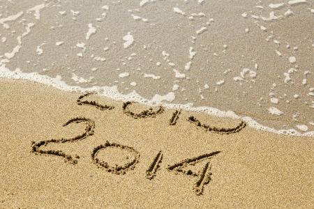 New Year 2014 is coming. Inscription 2013 and 2014 on a beach sand, the wave is covering digits 2013. photo