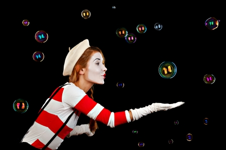 comedian: Portrait of the female MIM comedian catches bubbles, isolated on black background