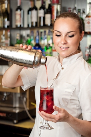 beautiful young barmaid making cocktail photo