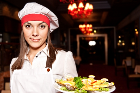 Young attractive female chef with dishes of mussels photo