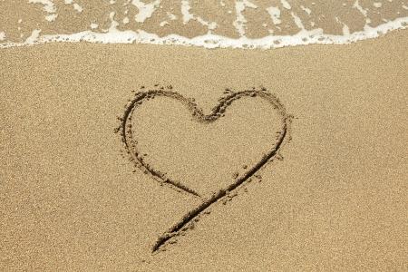 Heart drawn on the beach sand photo