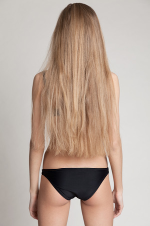 loose hair: Girl with loose hair standing standing back to camera. Natural image without make-up  and retouching. Stock Photo