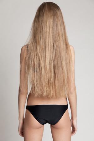 loose hair: La ragazza con i capelli sciolti in piedi in piedi di nuovo alla macchina fotografica. Immagine naturale, senza trucco e ritocco. Archivio Fotografico