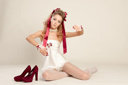 Young woman in the doll style with red bow and red shoes sitting on the floor photo