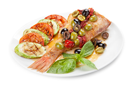 Grilled fish  with vegetables on a plate, isolated on white background Stock Photo