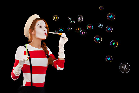 Portrait of the female MIM comedian blows soap balls, isolated on black background