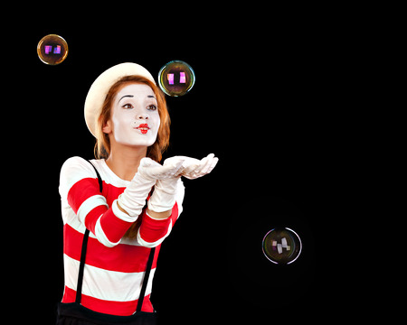 Portrait of the female MIM comedian catches bubbles, isolated on black background