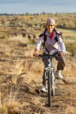 off road biking: Adult woman pedaling on a mountain bike on off-road
