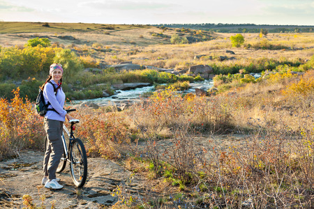 dult: ?dult woman standing next to a mountain bike and looking at the camera on a river and hills background