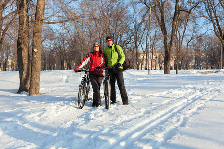Adult couple having a good time with the bikes in the  snow covered city park Imagens