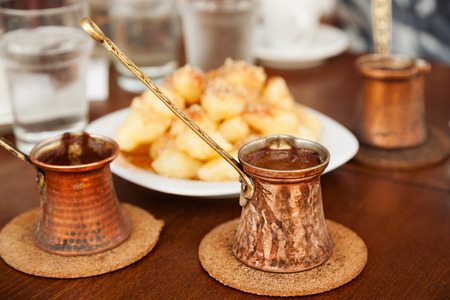 cezve: Coffee served in three pots  with three cups of water and traditional southern sweets. Small DOF.