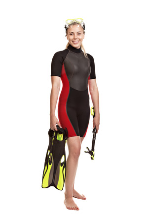 wet suit: Young smiling blond woman in a wet suit for swimming is in the full-length holding flippers and snorkel.Studio short. Isolated on white background. Stock Photo