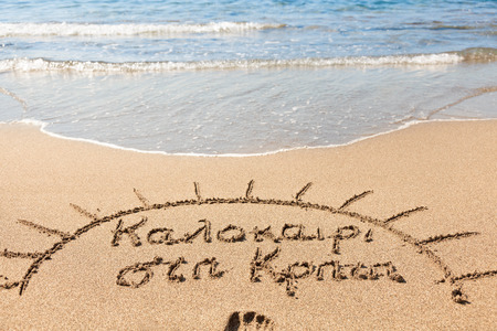 translates: Hand made text in sand on a beach - Καλοκαίρι στη Κρήτη,  which translates from Greek as Summer in Crete