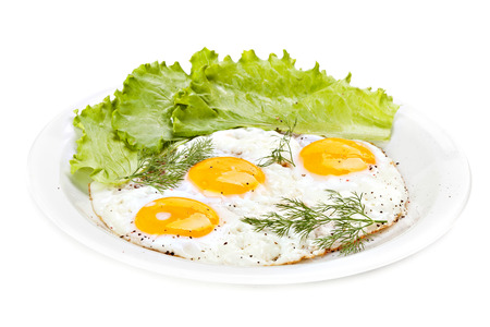 fried egg: Plate of traditional breakfast with fried eggs and herbs Stock Photo