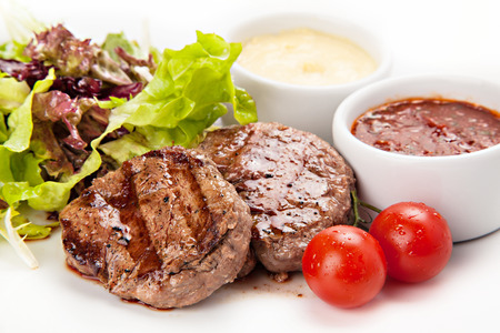 Barbecue Beef Steaks medium grilled with white and red sauces, lettuce and cherry tomatoes.