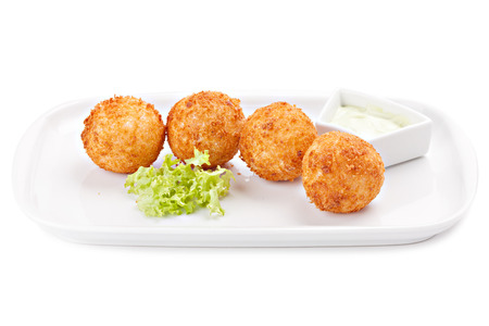 Deep fried cheese balls with lettuce and sauce, isolated on white background