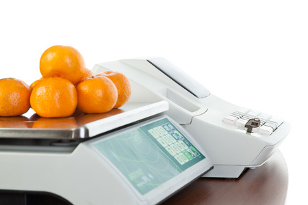Weighing of fruits on electronic scales, isolated on white background.
